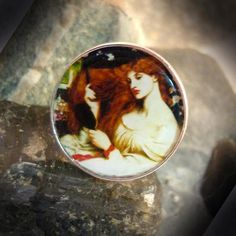 Lady Lilith - Round resin covered silver plated adjustable ring depicting Dante Rossetti's famous Pre-Raphaelite painting 'Lady Lilith'. Size - 2.4cm x 2.4cm. Price - £8.99