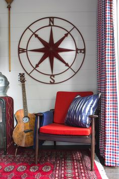 A reading nook showcasing an antique compass and Danish modern walnut chair upholstered in a rust orange fabric, elevates the room's transitional design approach. How cozy is this spot!? >> http://www.hgtv.com/design/hgtv-urban-oasis/2015/master-bedroom-pictures-from-hgtv-urban-oasis-2015-pictures?soc=pinterest