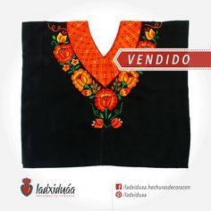 Huipil negro, con tejido de cadenilla en hilos color naranja y flores bordadas a mano.