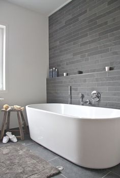 i think watching this tub fill with water would be a pleasure unto itself #bathroom White vanity and toiletblack tile and back