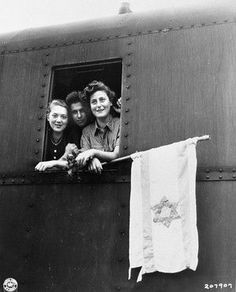 Three young Jewish DPs (displaced persons) look out of the window of their train holding a homemade Zionist flag as they depart from Buchenwald (the first German concentration camp on German soil) on the first leg of their journey to Israel.