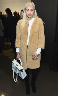 Sofia Richie wearing a long fuzzy coat, white long sleeve, and black trousers at the Rachel Zoe F/W 15 presentation // NYFW