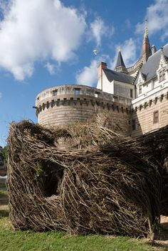 patrick dougherty weaves 'fit for a queen' at castle moat in nantes - designboom | architecture & design magazine