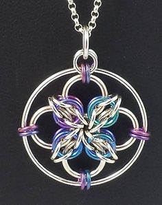 Hand-woven, and made out of high-polished sterling silver and anodized niobium, this pendant measures 1 inch in diameter, but is surprisingly lightweight. An excellent choice to add a bit of colour to your day, and of a size that makes it convenient for whatever you plan to do. Suitable for everyday wear. Length is 1 inch Weight is 4.1 grams Chain is not included with the pendant. Will provide a cord if requested.