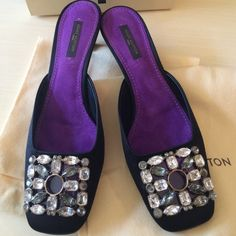 Louis Vuitton Black Satin &Crystal Mules Authentic Spectacular Louis Vuitton black satin mules with marquise, emerald cut, and round crystals on the embellished see through buckle. Features a regal purple suede innersole that adds an unexpected pop of color. Worn once indoors for a dinner party. In excellent condition and comes complete with two shoe bags and shoe box. 100% authentic. Louis Vuitton Shoes Mules & Clogs