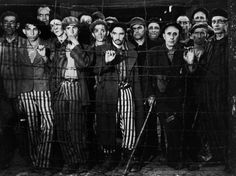 Survivors gaze at photographer Margaret Bourke-White and at their rescuers from the United States Third Army during the liberation of Buchenwald, April 1945.
