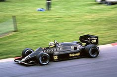 Ayrton Senna in the JPS Lotus 98T about to enter Paddock Hill Bend at Brands Hatch. An amazing corner, over a crest right, sharply down hill, bottom out suspension and up the otherside into a 180.   It takes guts to accelerate into that bend.