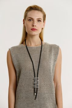 This long silver color-plated necklace is made from black rubber and metal stripes that echo the timeless design of a ladder. This piece is the perfect way to complete to just about any look, from casual to elegant and everything in between. If you're looking for a unique necklace that makes any outfit more interesting and attractive, this necklace is a great choice.