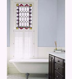A reproduction claw-foot tub and marble-topped double vanity complement the original stained glass window in this 19th Century Row House bath. | Photo: Matthew Millman | thisoldhouse.com