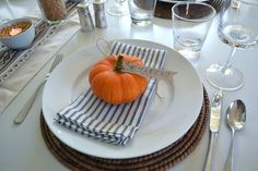 Fall Placesetting.....white plate, rattan charger, ticking stripe napkin, and simple pumpkin. With blue placemats, I would skip a tablecloth. @Lindsey Atha this is sort of what I had in mind.