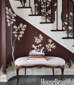 On the entry's chocolate-brown walls — Benjamin Moore Aura in Mink — Sommers had Patrick Roullier paint a mural of ivory trees and squirrels based on the flora and fauna of the Illinois countryside. The bench from the Antique & Artisan Center is covered in a Pindler & Pindler ticking stripe.   - HouseBeautiful.com