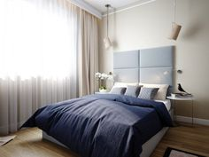comfy bed with blue headboard features white bedside tables and hanging bedside lamps