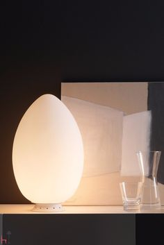 Uovo table lamp has a metal frame in white finish and a frosted white blown…