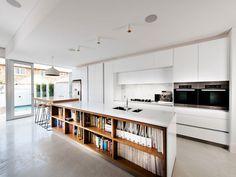 Cucina moderna aperta sul soggiorno con mobili bianchi e isola rivolta verso l'esterno