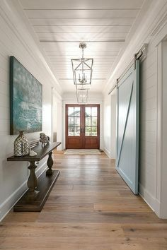 Exquisite blue and white foyer features Darlana Medium Lanterns hung from a shiplap ceiling over sawn oak floors and lighting a balustrade console table topped with a mercury glass door positioned under a deep blue abstract painting mounted on a shiplap wall facing a blue barn door on rails.