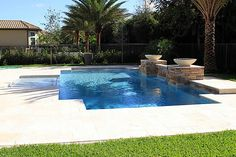 This pool features a marble deck, custom waterfall, sundeck, fire bowl features and lush landscaping