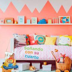 Un muro que recuerda las montañas y cojines de muchos colores harán de la habitación de tu pequeña un lugar lleno de alegría.