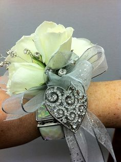 Rose corsage with a decorative wrist band and heart.
