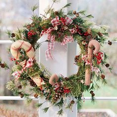 Three fabric candy canes and red plaid bows are important enough to be the only decorations for this artificial pine wreath.