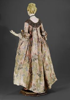 Back view of a rare female mannequin wearing a robe à la francaise, France, c. 1765.  Mannequin: painted wood, blond wig. Robe: pink silk brocaded with floral sprays and metal thead embroidery.