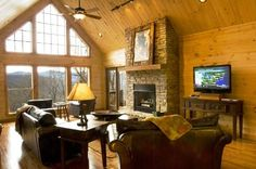 The living room at Millstone Lodge with leather sofas and a gas fireplace.