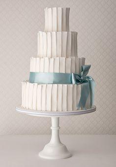 Textile panels and satin wedding cake: Chocolate fudge cake, orange zest butter cream, sugar textile panels with a satin ribbon bow.