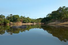 This is a water surface reflection landscape photograph of an Orinoco River inlet, Amazon State, Venezuela.