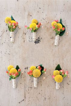 Wedding boutonnieres of yellow billy balls, peach hypericums, and coffee berries, wrapped with twine.