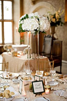 Gathered flowers in tall vases and tea lights around