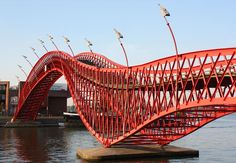 Python Bridge AMSTERDAM: A glimpse of this shapely red pedestrian span explains its name. One of the latest additions to the city's canal crossings (opened in 2001), it packs up well. The bridge was designed to be dismantled every five years for the Sail Amsterdam maritime festival.
