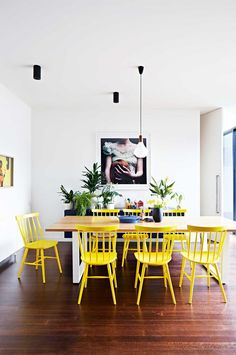 Dining room: bright yellow Ercol chairs, wooden rectangular dining table with white legs, timber floorboards, exposed lightbulb pendant light