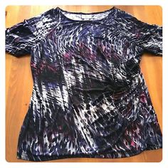 Worthington Top Very flattering short-sleeved stretch top with ruching at side. Purple, pink white and black pattern. 95% polyester, 5% spandex. Worthington Tops Blouses