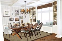 Love the built-ins flanking the giant window, the window seat, and the white planked wall.