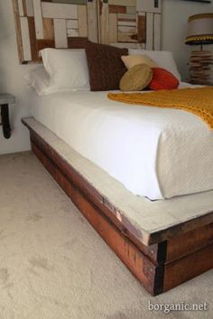 Really neat platform bed made out of salvaged wood and doors.  The headboard is salvaged wood on a sliding rail that hides built-in storage.