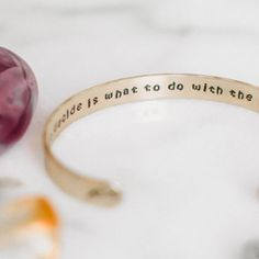 "Make a statement on your arm and set an intention in your heart with this inspirational quote bracelet. The inside features the quote by J.R.R. Tolkien, ""All we have to decide is what to do with the time that is given to us."" An arrow and a feather are on the outside ends."