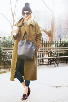 Blair Eadie of Atlantic-Pacific stays cozy during the cold NYC months in an olive coat, striped tee, beanie and signature red lips