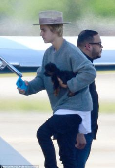 Boy's best friend: Justin Bieber looked like he needed a pal as he boarded a private jet o...