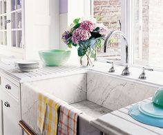 Farmhouse sinks can also be made with composite, fireclay, vitreous china, solid-surfacing, stainless steel, and stone. This deep-basined apron-front sink is paired with a countertop with deep grooves that channel spilled water back into the sink.