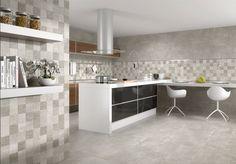 Cocina tipo isla, color en blanco y puertas acabadas en madera y negro brillo. Chapado en gris cemento, con cenefa en tonos claro y grises, a juego con el suelo. y el resto de