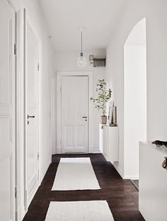 Struggling to decorate your long, narrow hallway? We have 19 long narrow hallway ideas that range in difficulty. From painting one wall to adding a long runner, we've got you covered. Turn your hallway into a library, or add shoe storage. All White Room, White Rooms, White Walls, White Space, Small Entryways, Small Hallways, Scandinavian Apartment, Scandinavian Home, White Apartment