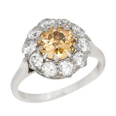Circa: 1920 Fancy Brownish Yellow Diamond Ring. Circa: 1920 Platinum Ring centrally set with an Old European Cut Diamond weighing 1.10 Carats and Grading as A Fancy Brownish Yellow in Color and I1 in Clarity. Further surrounded by 1 Carat of Old European cut Diamonds that are F in color and VS to SI in Clarity.