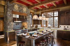 Consider your ceiling, otherwise known as the forgotten fifth wall, when decorating your kitchen. This neutral kitchen gets a wonderful punch of color via the hot red painted tile ceiling.