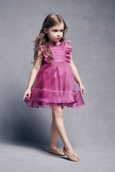 A beautiful 100% silk dress by Nellystella with ruffles, pleating details at the bodice and a sash bow at the back in a lovely rich botanical color. Fully cotton lined with a tulle underlayer and a zi
