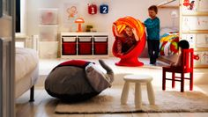 Swivel chair and children's furniture in a playroom.  I like the Tivoli storage featured in this room.  Depending on the bucket color choices you make, it can definitely grow with your child.  The bucket chair no doubt makes a great reading space too!  The art display at the end of the bed is an adorable bonus!