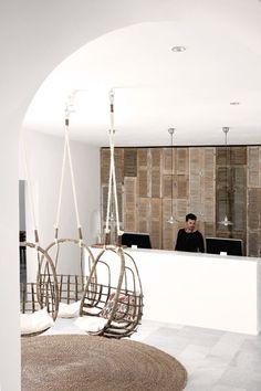 Entrada- recepción de un hotel con persianas recicladas de madera decorando toda la pared.