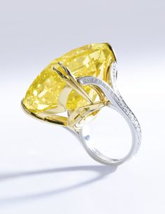 SENSATIONAL AND RARE FANCY VIVID YELLOW DIAMOND RING, GRAFF, KNOWN AS 'THE GRAFF VIVID YELLOW' Featuring a cushion modified brilliant fancy vivid yellow diamond weighing 100.09 carats, the shoulders embellished with brilliant-cut diamonds, size 50, signed Graff, diamond detachable from band and may be worn as a pendant, case by Graff.