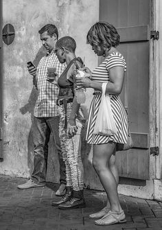 Connected Disconnect Bw.  Three people have left the camaraderie of a Bourbon St bar in the French Quarter of New Orleans to connect with the world via their phones. Their apparent isolation strikes me as deeply ironic. B&W version.