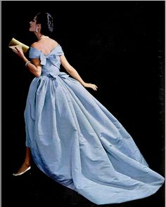 1957 Simone in blue silk faille ball gown, skirt trails in the back from shorter hem in front, bodice is fastened by two bow knots in back, by Jean Patou,