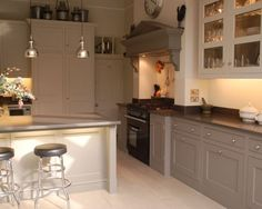 photo of classic traditional grey hello of mayfair kitchen with fireplace and range cooker glass fronted cabinet