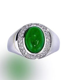 A jadeite jade and diamond ring  centering a jadeite jade cabochon, measuring approximately 10.2 x 7.5 mm., within a double tiered surround of round brilliant-cut diamonds; mounted in eighteen karat white gold